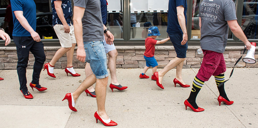 Group of men walking while wearing red high heels. Picture taken from side view.