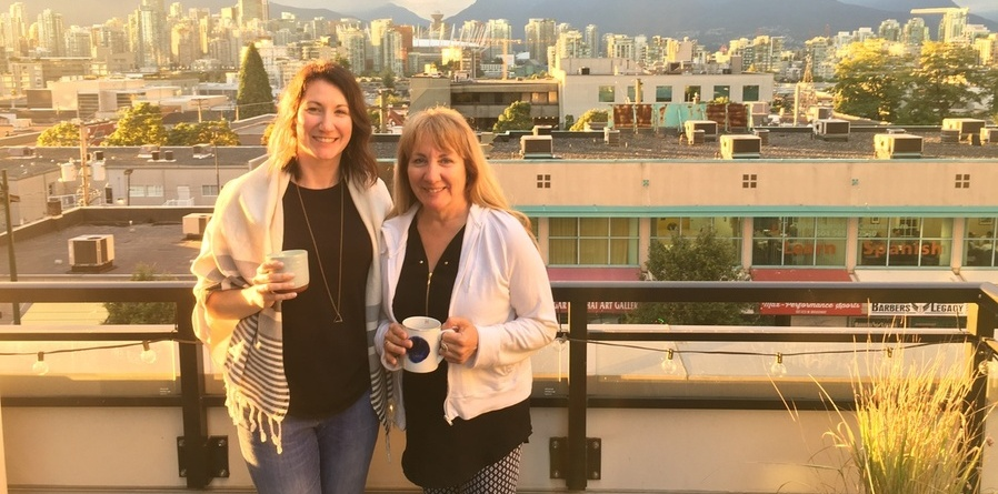 Colleen is pictured standing in front of a cityscape, beside another woman. Both are holding coffee mugs and smiling.