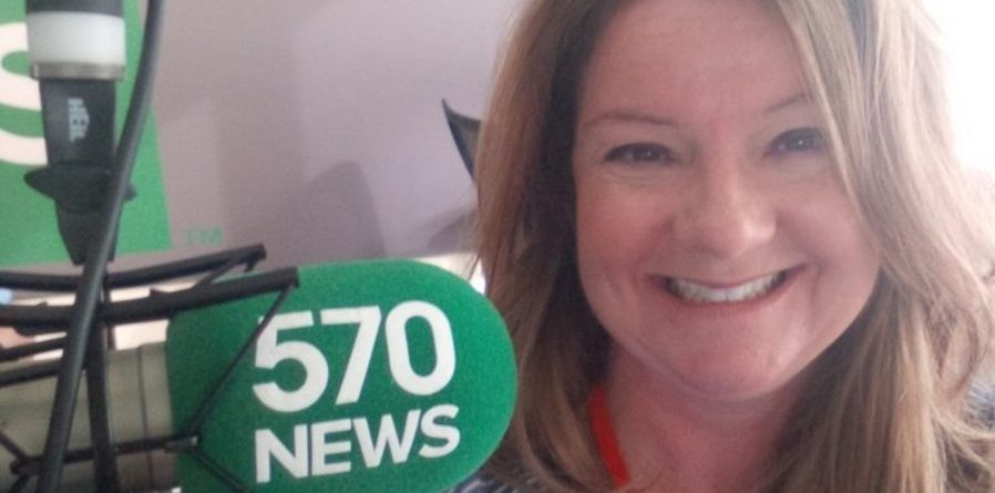 Lisa pictured smiling beside her microphone with the 570 news logo on it