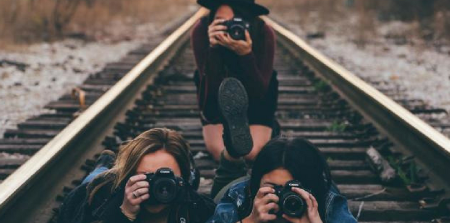 three girls holding cameras in front of their faces