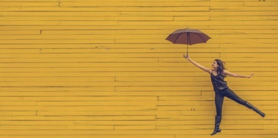 Woman holding an umbrella in front of yellow brick wall, leaping in the air.