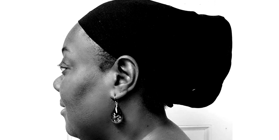 A black and white close-up of Lisa, side view. She's wearing a black scarf over her hair.