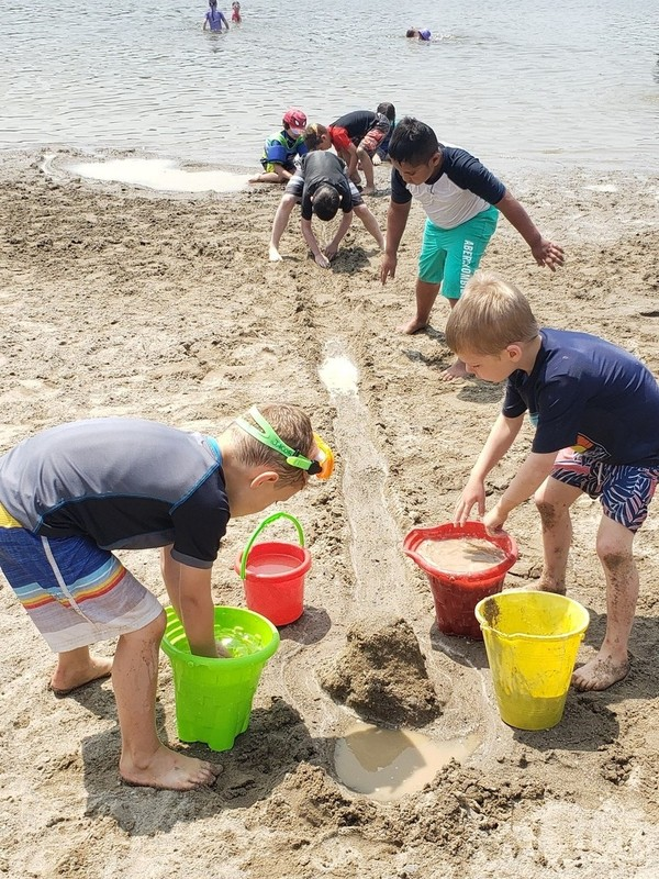 Shade's Mills summer campers play on the beach with buckets
