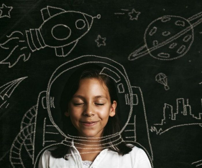 Young girl with her eyes closed, smiling against a chalk board filled with drawings of space exploration
