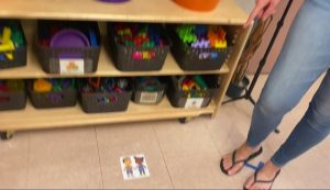 A shelf with bins on it, a sticker on the floor shows two people