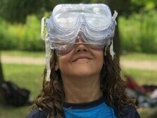 girl wearing multiple safety goggle sets over her eyes is smiling