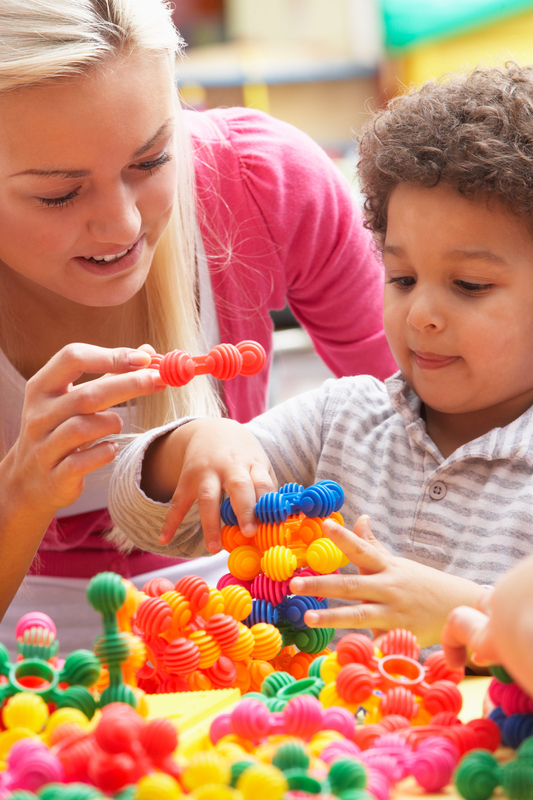 teacher helps small boy play with colourful plastic toys