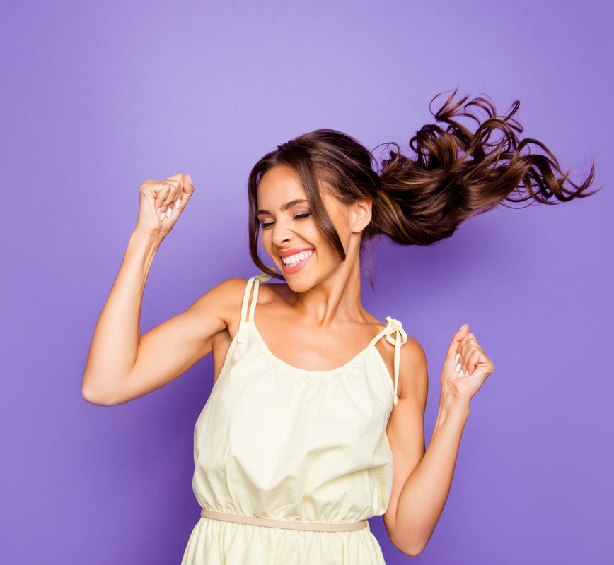 Happy woman dancing and smiling on purple background