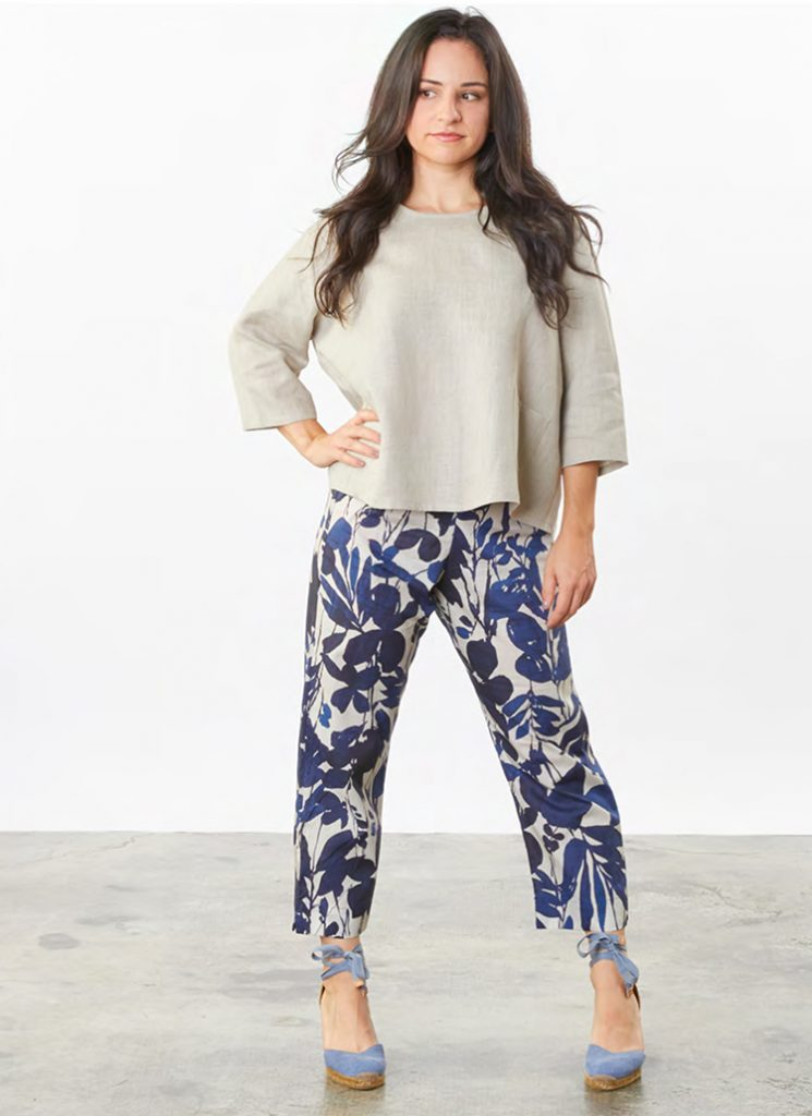 A woman stands with one hand on her hip. She's wearing blue floral pants by Bryn Walker and a beige linen top by Bryn Walker.