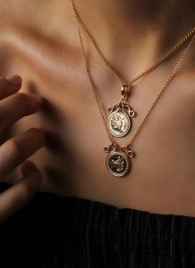 Close up of woman's collar bone area. She's wearing two pendant necklaces on gold chains.