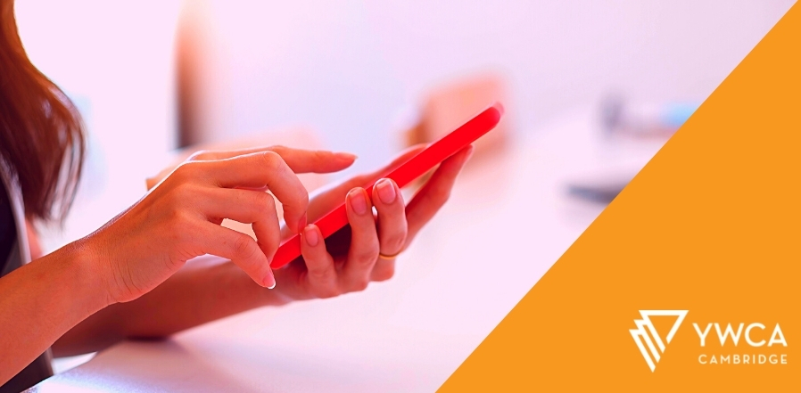 Photo showing hands holding a cell phone, one hand hovering over the screen. Orange triangle fills the right side of the image, and on it is the YWCA Cambridge logo