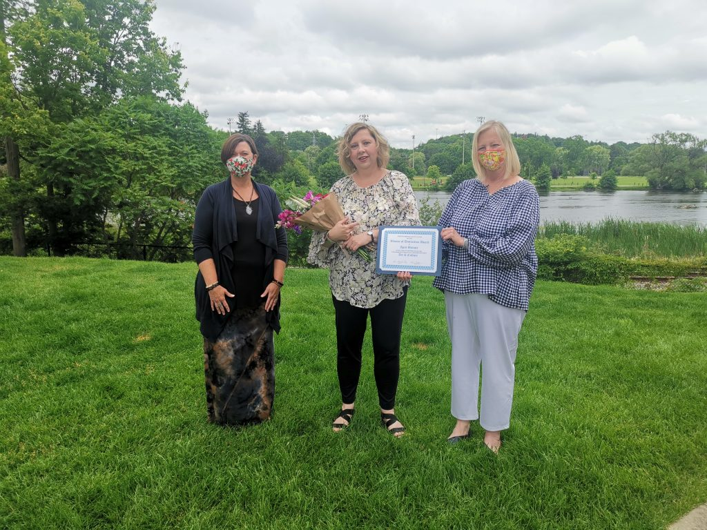 April stands on a lawn and there is a body of water behind her. On her left is YWCA Cambridge CEO, Kim Decker and on her right is YWCA Cambridge board member, Sarah Daly