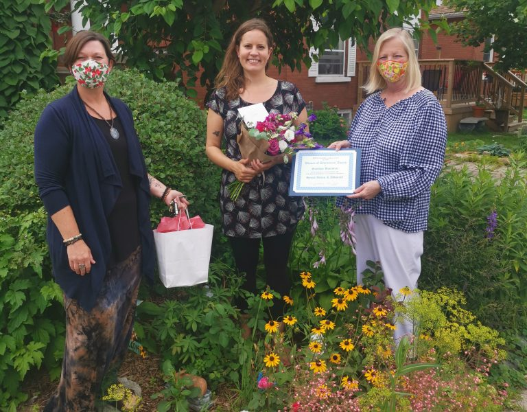 Siobhan stands in a garden holding a bouquet of flowers. On her left is Kim Decker, CEO of YWCA Cambridge and on her right is Sarah Daly, YWCA Cambrdge board member.
