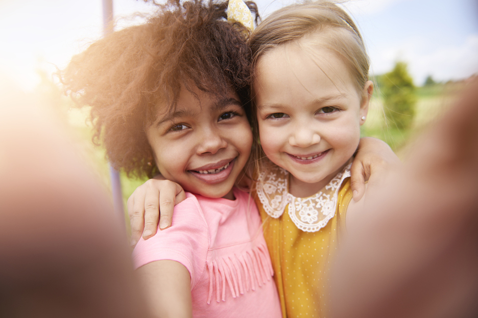 Two smiling girls in child care smiling at the camera with their arms around each others shoulders.
