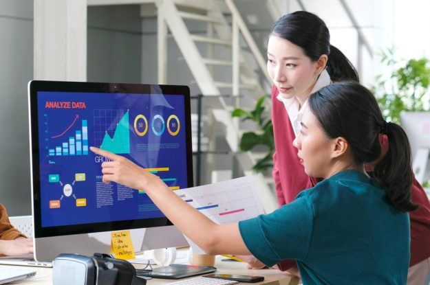 Two women analyzing data on a computer screen